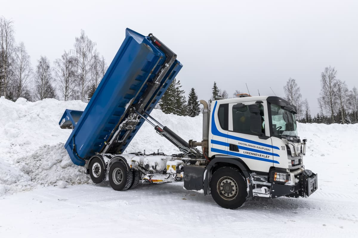 Kuorma-auto kaataa lunta kasaan Viitasuon lumenkaatopaikalla.