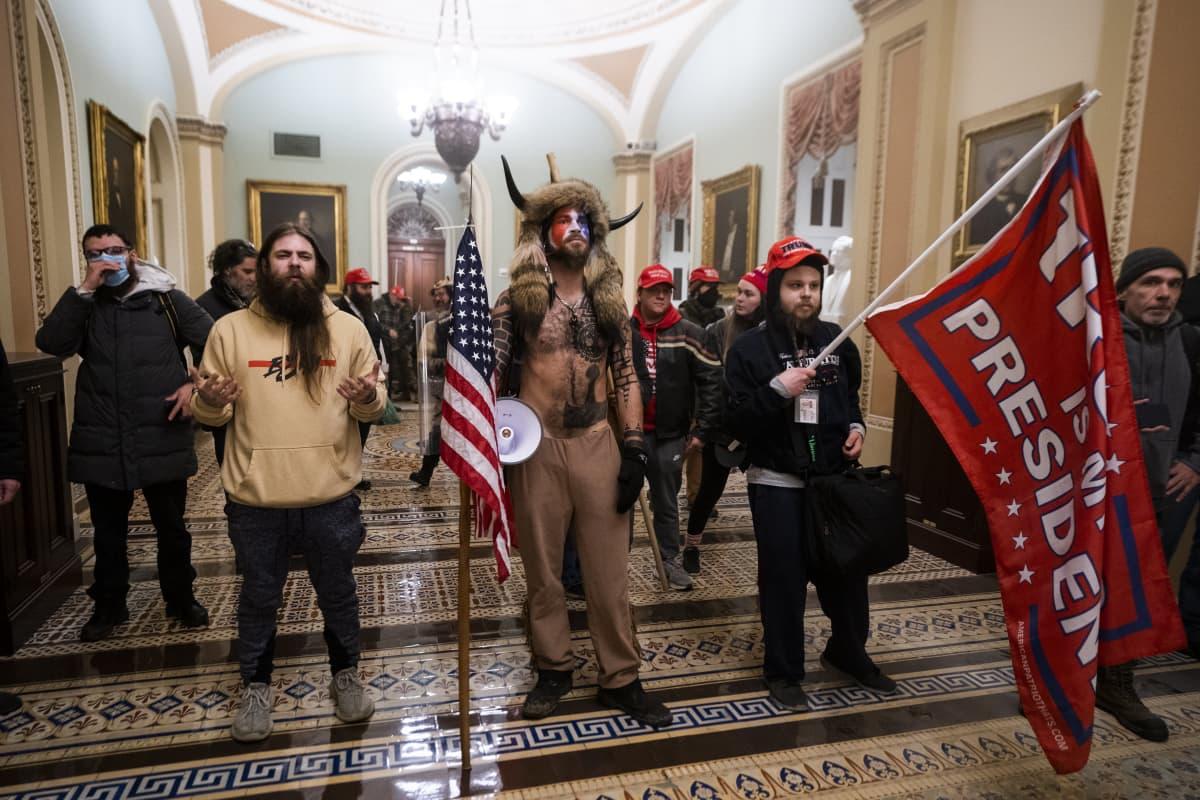 Kongressiin tunkeutuneet seisoivat ryhmäpotretissa. Jacob Chansley keskimmäisenä.