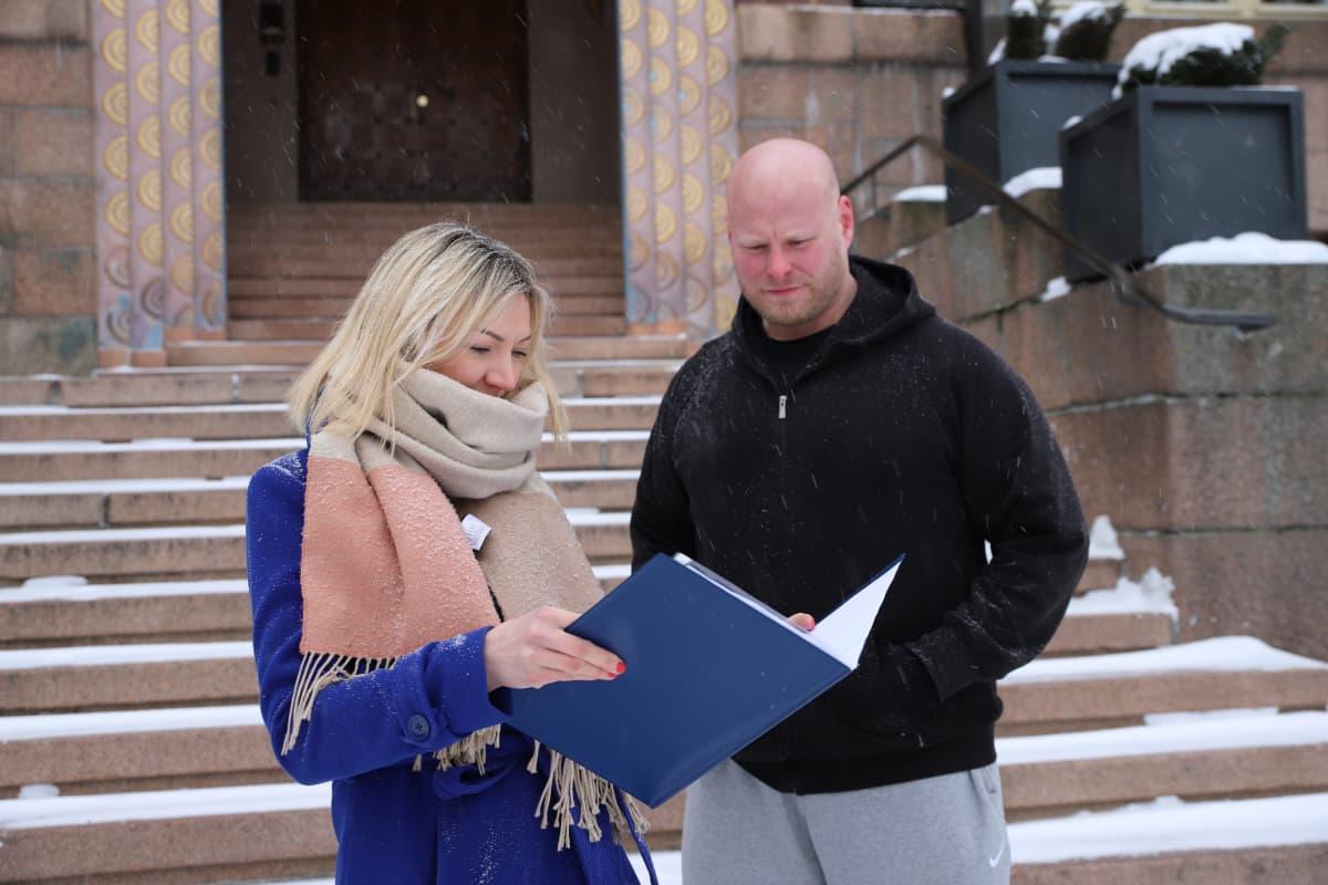 Pro Lahden Anita Immonen ja Kalle Aaltonen tutkivat kuntavaaliehdokaslistaa kaupungintalon edessä