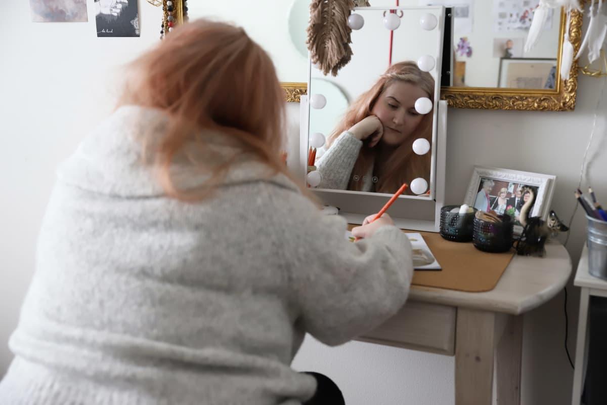 Kotkalainen Saara Niemi kirjoittamassa asunnossaan.