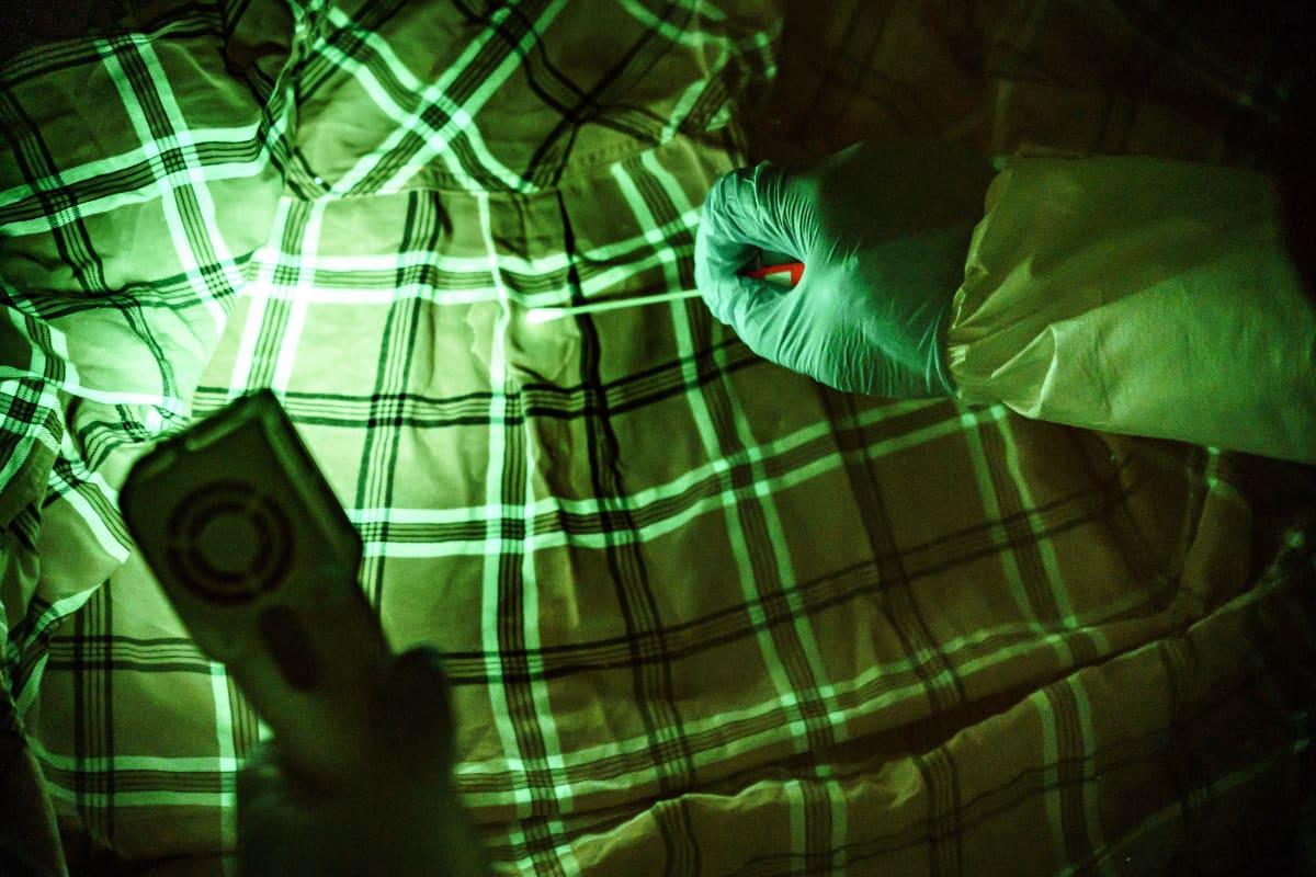 Rikospaikkatutkija on löytänyt tahran paidasta ultraviolettivalon avulla. Käyttämällä keltaista suodatinta silmälaseissa tahra saadaan silmälle näkyväksi.