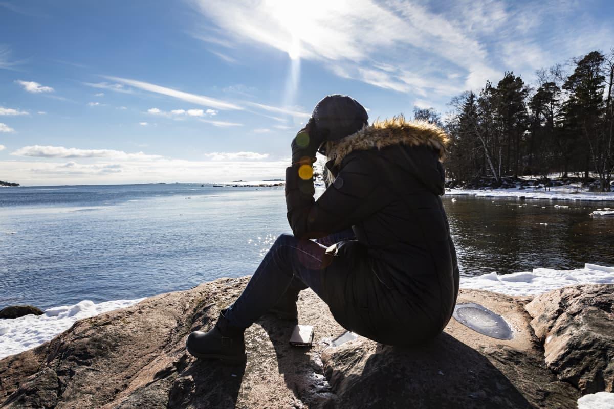 nainen istuu kalliolla