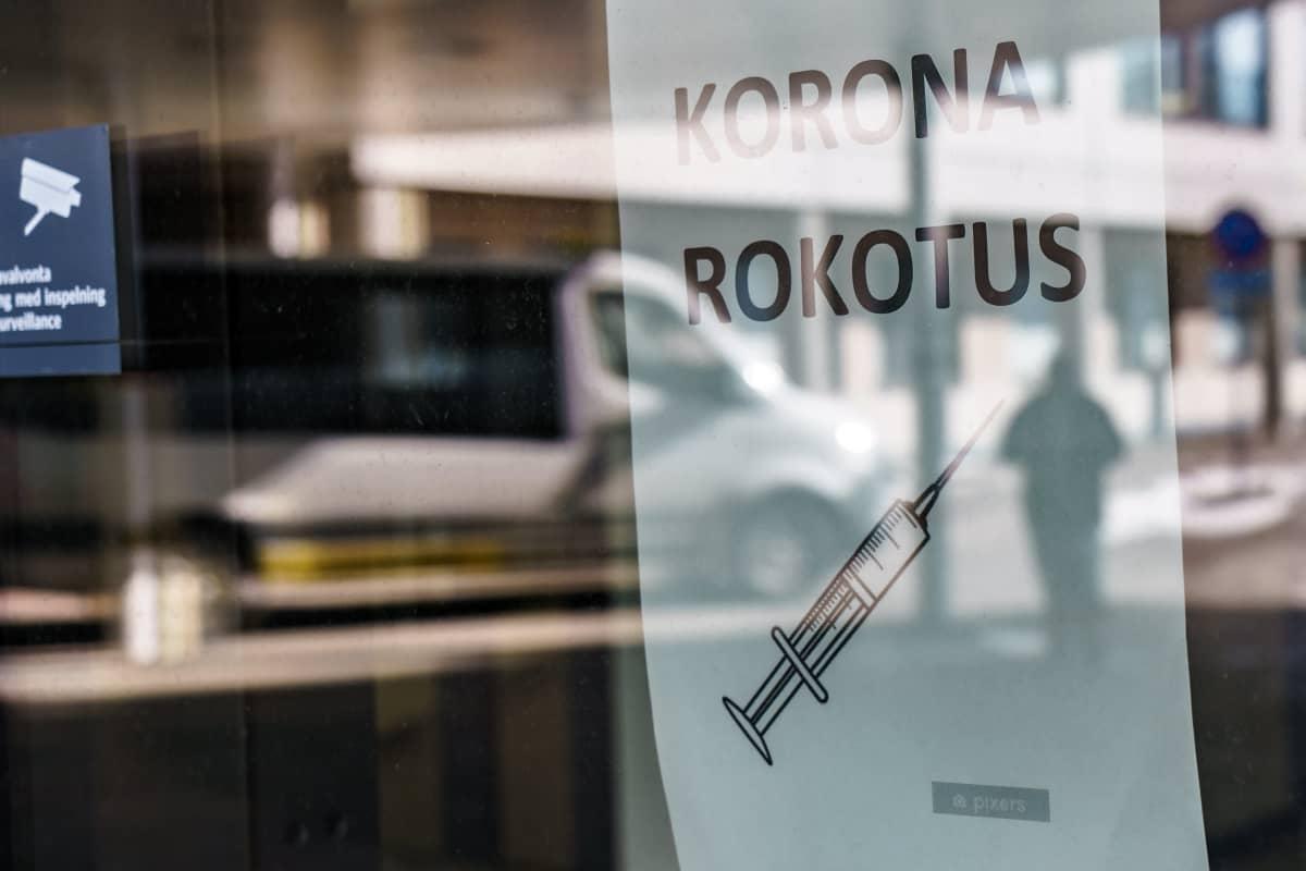 Koronarokotuspaikan lasiovesta heijastuu  ihmisen hahmo. Ikkunassa lappu, jossa lukee koronarokotus.