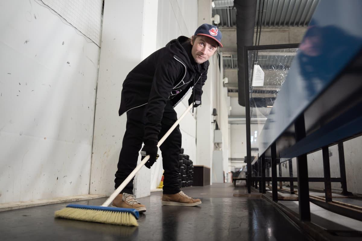 Yhdyskuntapalvelukseen tuomittu Juhani Saunio poseeraa jäähallilla jääkiekkoasennossa harjan kanssa.