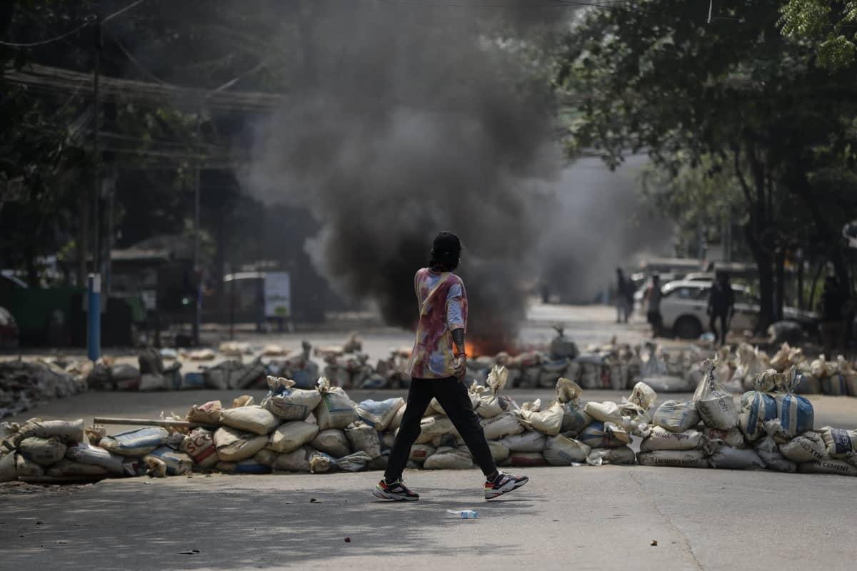 Mielensosoittaja käveli savuavien barrikadien keskellä Yangonissa 27. maaliskuuta 2020.