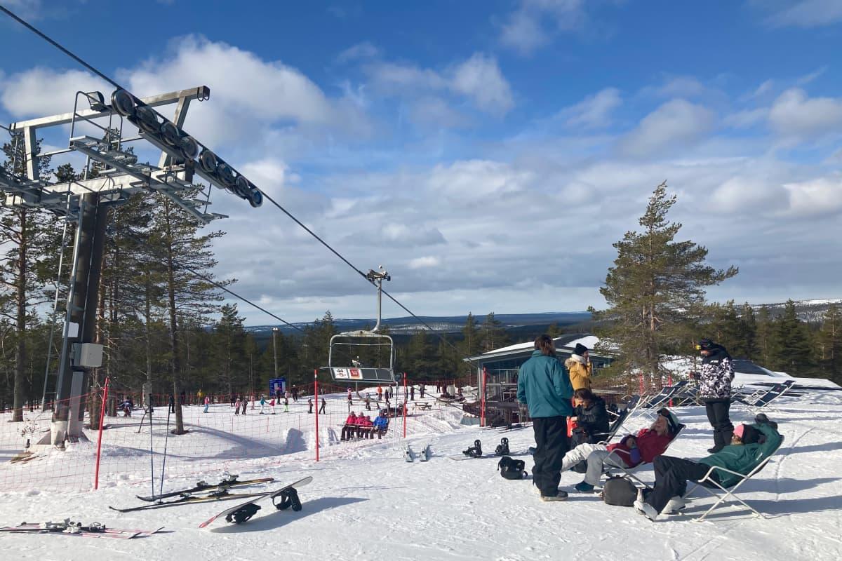 Lasketteluasuisia ihmisiä lekottelee lepotuoleissa hiihtohissin vieressä lumella Ylläksen laskettelukeskuksessa.