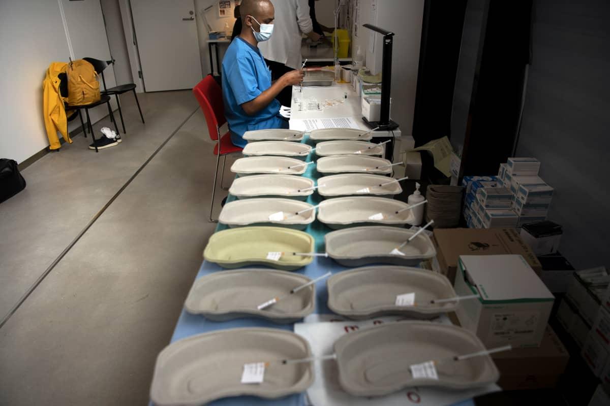 Sairaanhoitaja valmistelee koronarokotteita.