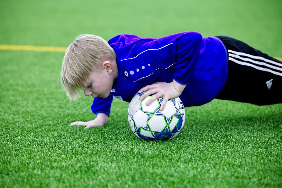 Lapsi treenaa jalkapalloa.