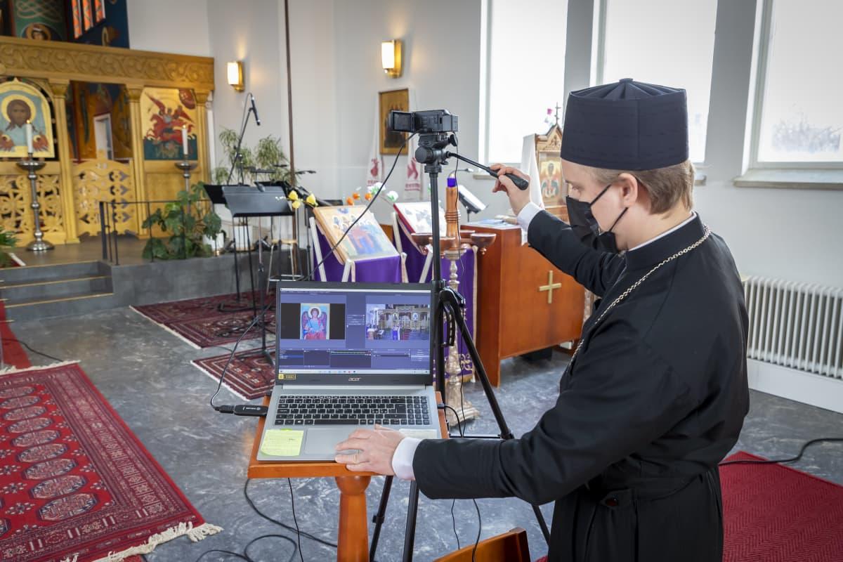 Pappi kokeilee kameraa ja tietokonetta kirkkosalissa etäjumalanpalvelusta varten