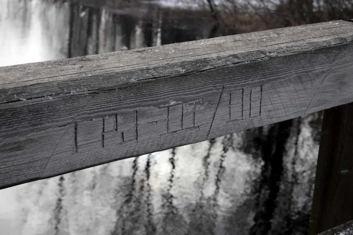 Puiseen sillan kaiteeseen on kaiverrettu sillan tekijöiden puumerkki