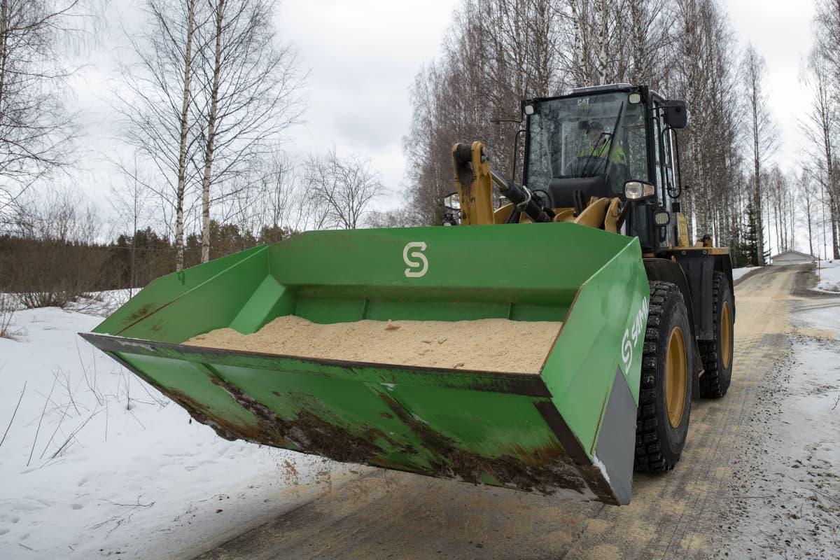 Koneenkuljettaja Santeri Tolppanen kuljettaa traktoria, jonka kauhassa on liukkaudentorjuntaan tarkoitettua sahanpurua.