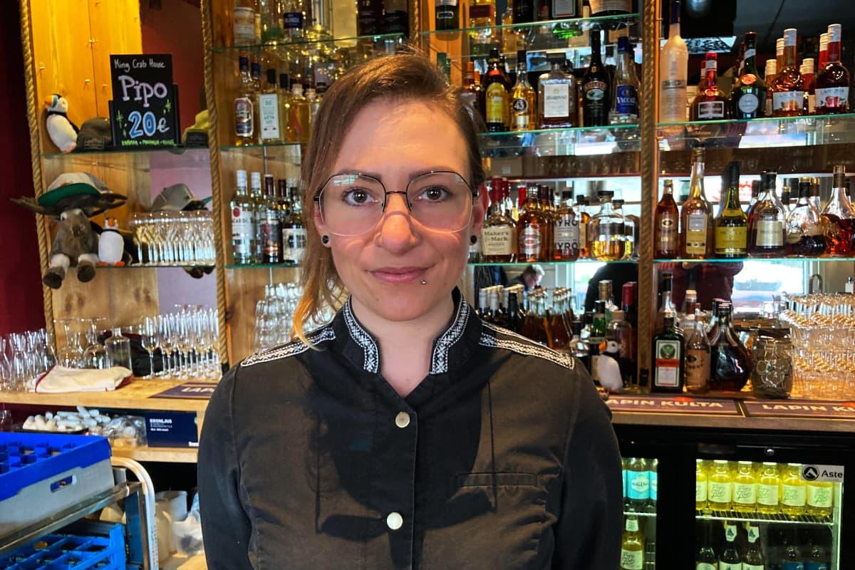 Silmälasipäinen nainen mustassa ravintolakokin takissa seisoo ravintolan tiskin takana, taustalla peilejä ja viinapulloja.