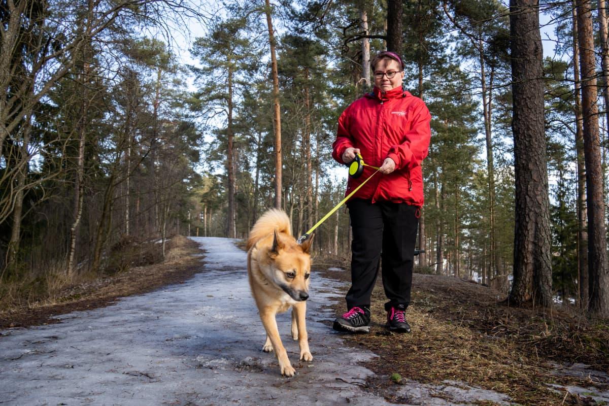 Heli Tuikka lenkillä koiransa kanssa.