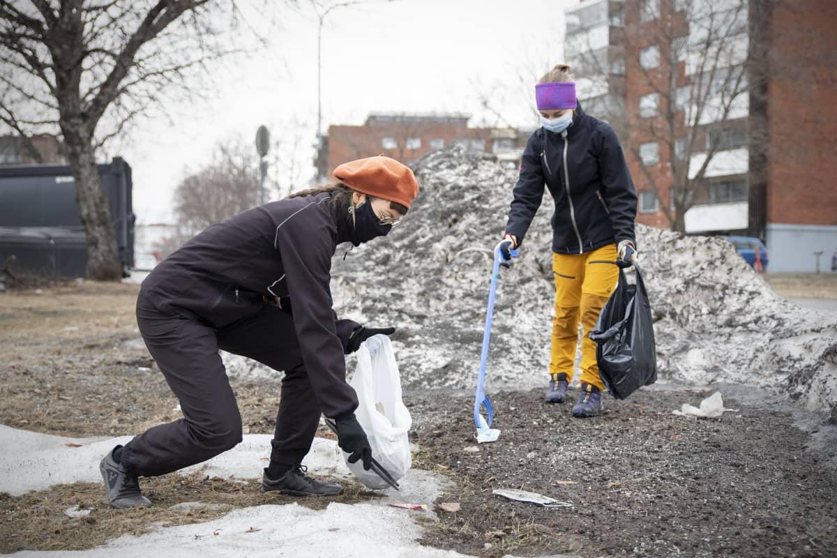 Juni Sinkkonen ja Eveliina Korkiatupa keräävät pihdeillä roskia maasta.