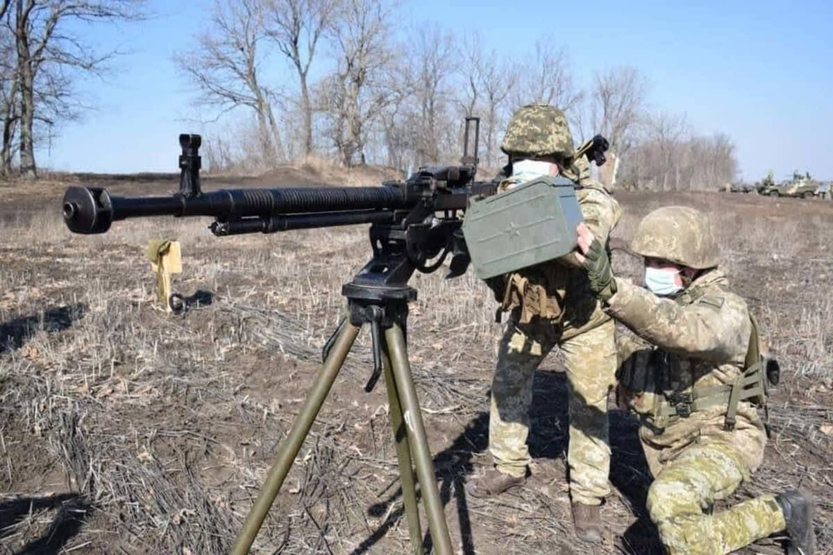 Kaksi maastopukuista sotilasta on raskaan konekiväärin ääressä. Toinen tähtää konekiväärillä ja toinen nostaa panoslaatikkoa. Taustalla näkyy lehdettömiä puita.