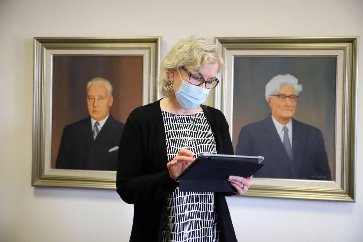 Sysmän kunnanjohtaja Marketta Kitkiöjoki käsittelee tablettia sisätiloissa.
