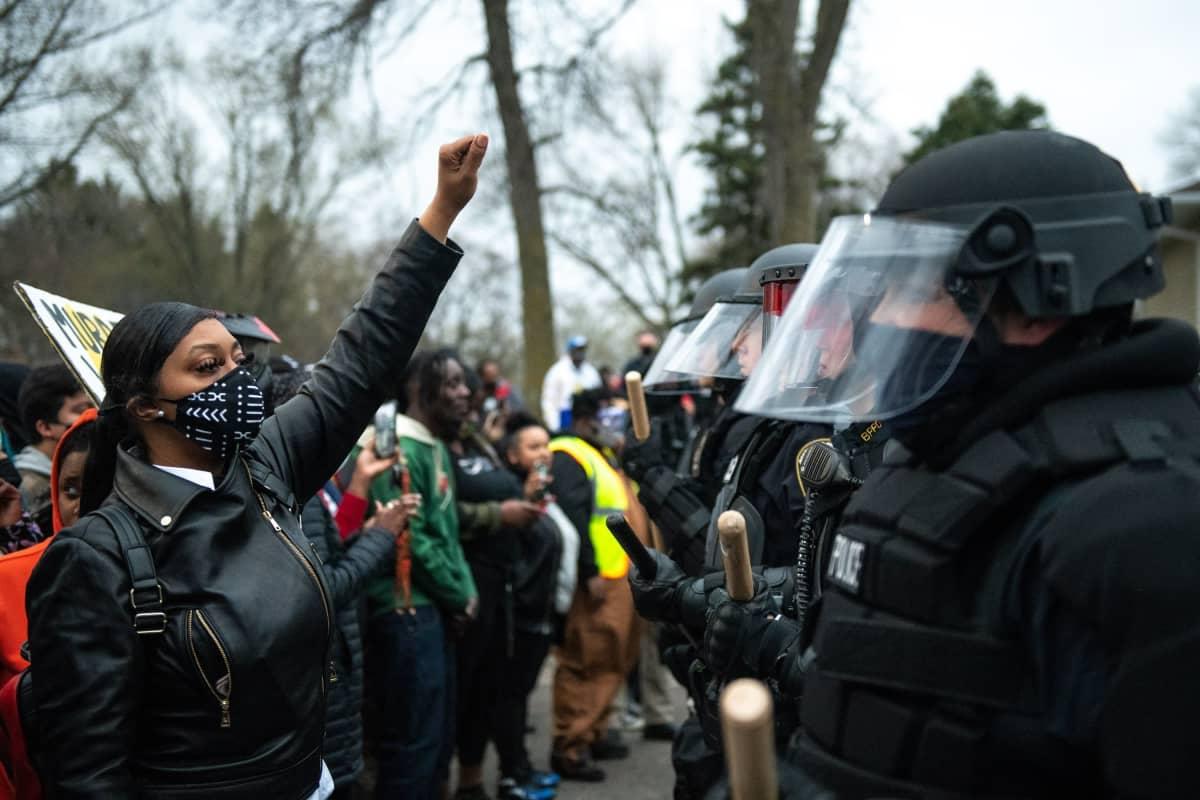 Mielenosoittajien rivistä erottuva tummaihoinen nainen nostaa nyrkkiään ilmaan mellakkavarusteisten poliisien edessä
