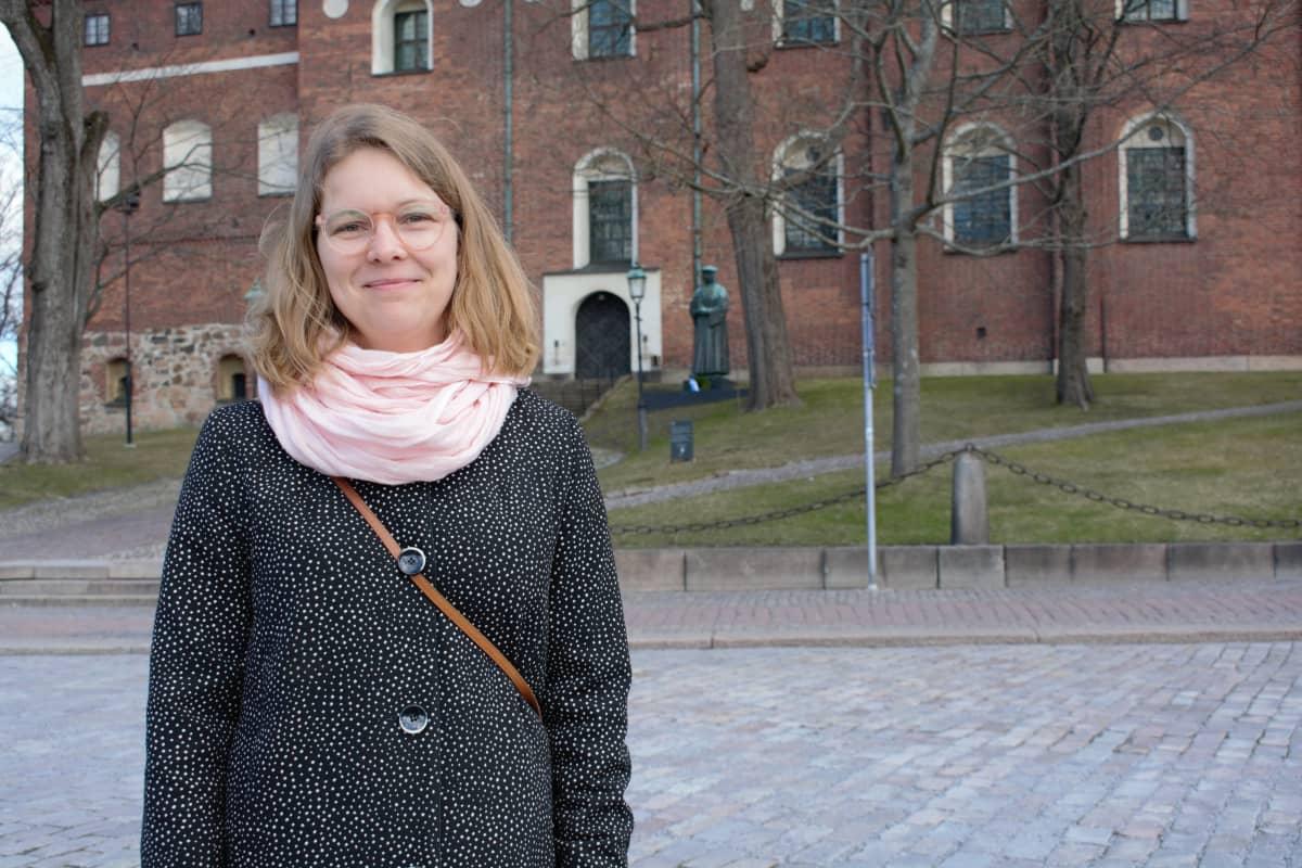 Väitöstutkija Mari Välimäki Turun tuomiokirkon lähellä.