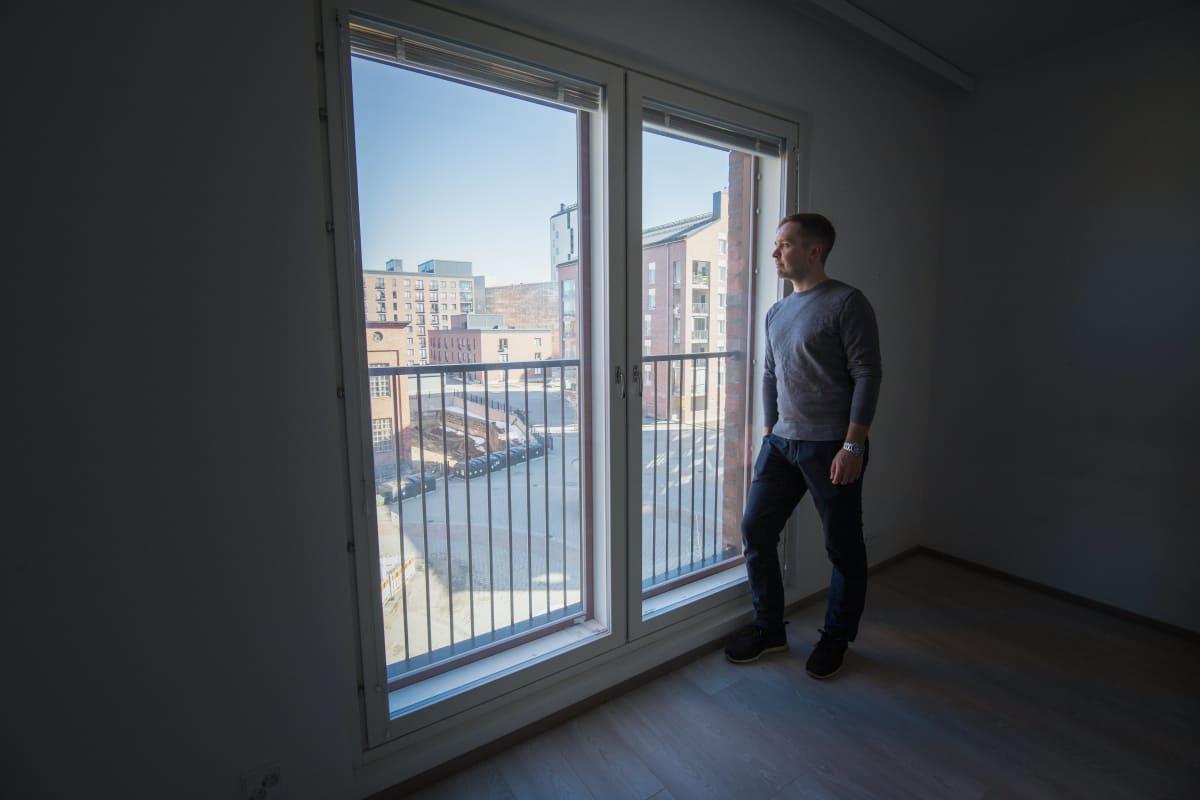 Kiinteistönvälittäjä Tero Tupamäki katselee maisemaa sijoitusasuntonsa ikkunasta.