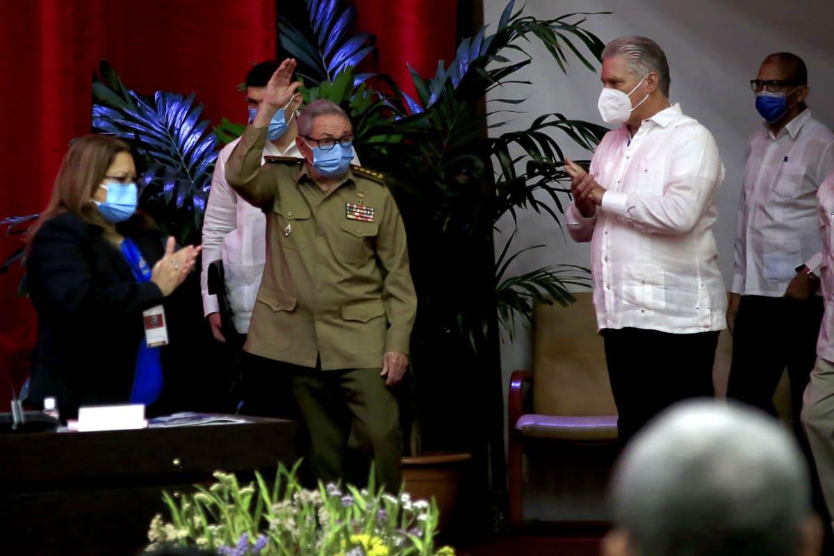 Miguel Diaz-Canel taputtaa, kun Raul Castro vilkuttaa yleisölle lavalla.