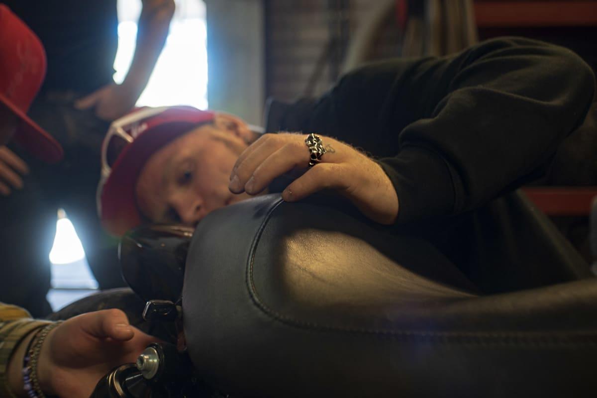 Mies nojaa moottoripyörän satulaan kädellä jossa iso kultasormus.