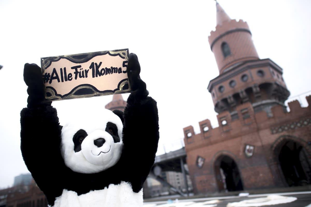 """Panda-asuun pukeutunut ihminen pitelee kylttiä jossa lukee saksaksi """"Kaikki 1,5:n puolesta"""""""