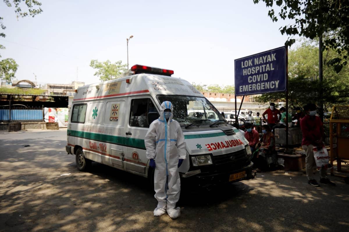 Ambulanssi seisoo sairaalan kyltin luona. Ambulanssin edessä seisoo ihminen täydessä suoija-asussa.