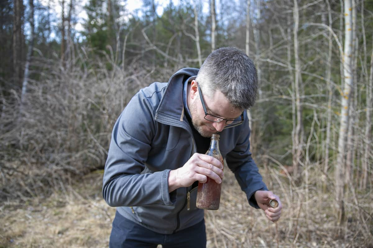 Mikko Keränen haistaa löytyneen pullon sisältöä.