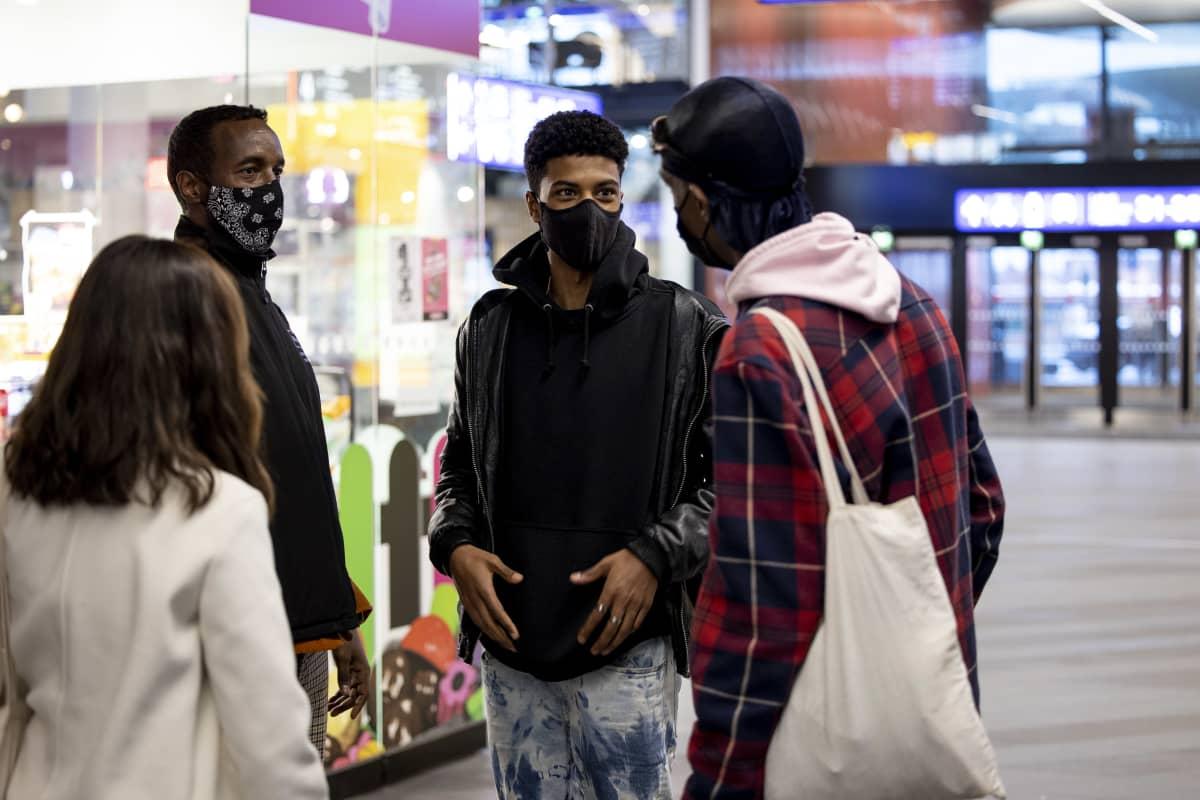 Nuoret  ja etsivän nuorisotyön työntekijät juttelee kauppakeskuksessa