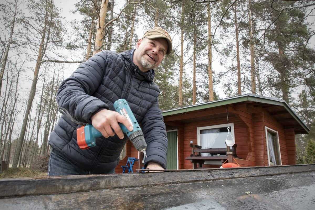 Hymyilevä Kari Kulmala korjaa puuvenettään rantasaunan luona.