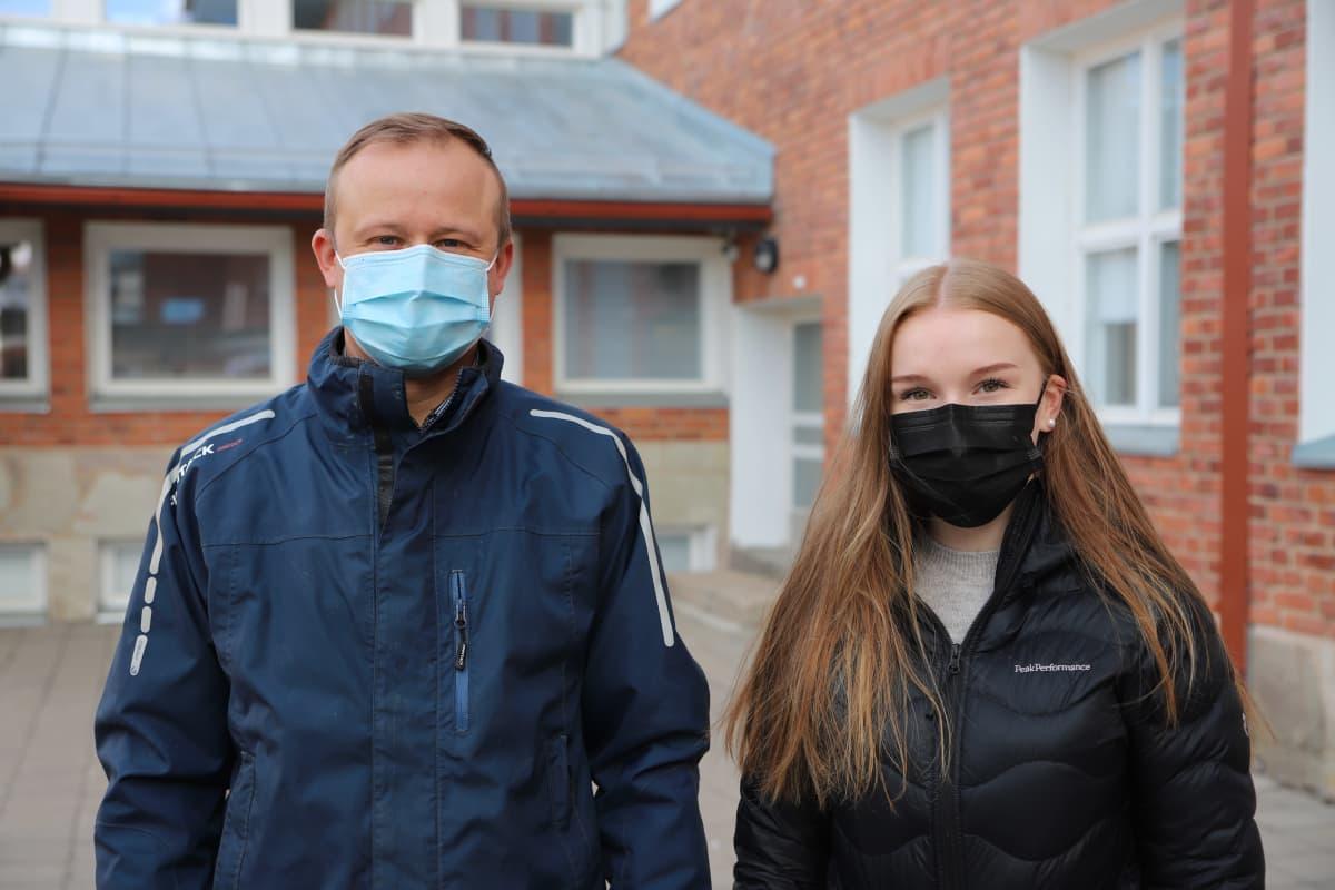Osmo Rauhala ja Unna Karppinen seisovat Rovaniemen Lyseonpuiston pihalla maskit päässä.