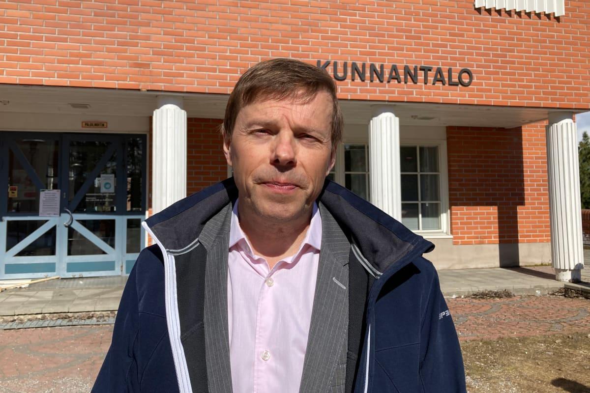 Timo Kurula katsoo kameraan silmiään siristellen ja takki auki, taustallaan Kittilän kunnantalo.