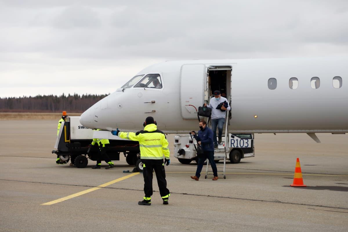 Keltatakkinen maapalveluhenkilökunnan edustaja viittoo Kemi-Tornio lentokentällä, taustalla matkustajakone, josta laskeutuu matkustajia.