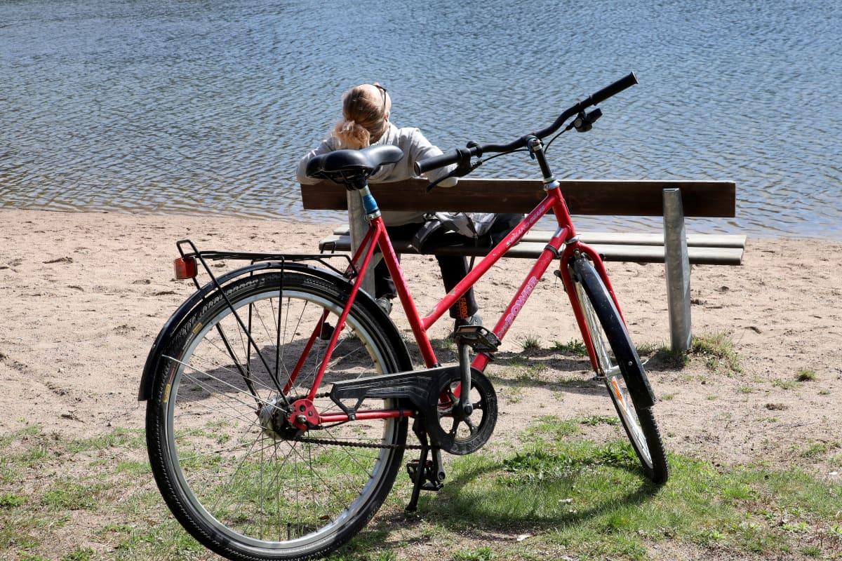 Pyöräilijä pysähtynyt Lahden Mytäjäisten uimarannalle penkille istumaan, kasvot kohti aurinkoa.