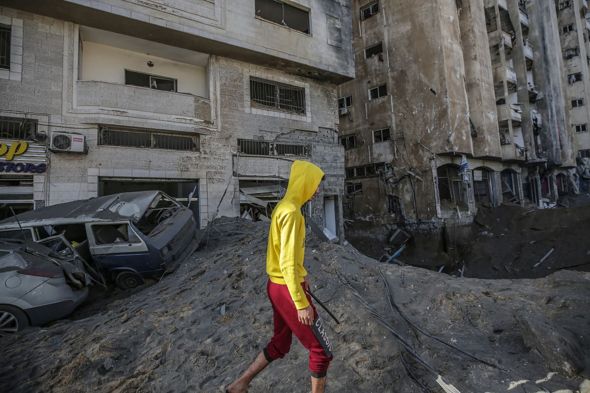 Poika kävelee öisten ilmaiskujen tuhojen ohitse Gazan kaupungissa keskiviikkona.