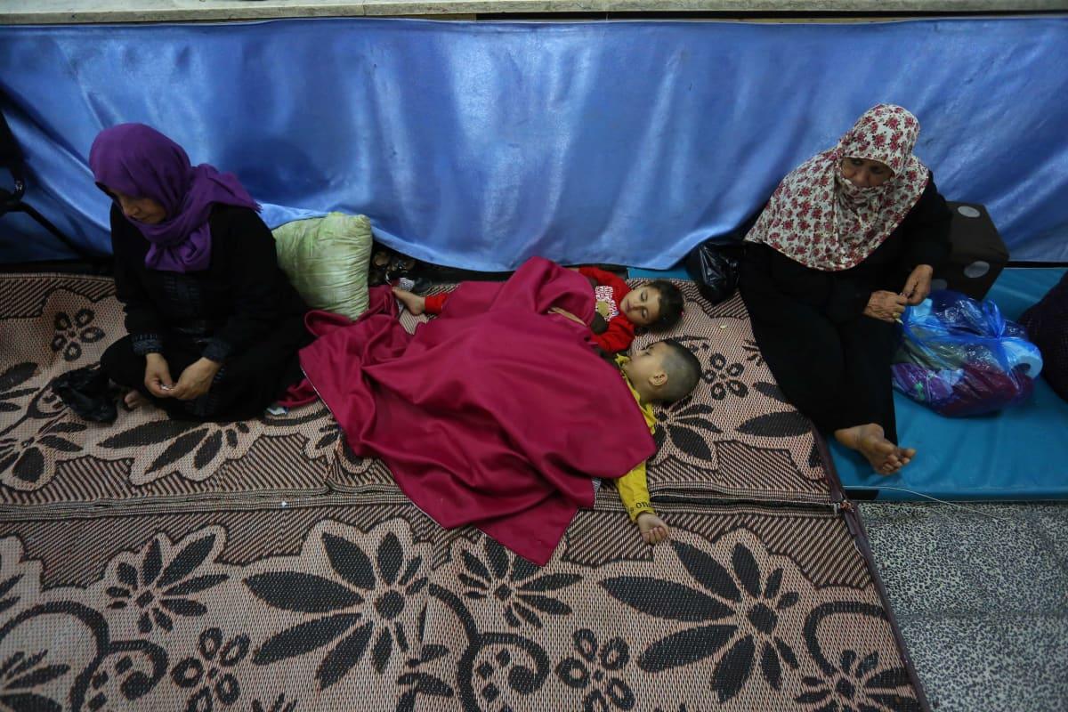 Kaksi palestiinalaisnaista istuvat koulun lattialla Gazassa vieressään kaksi nukkuvaa lasta