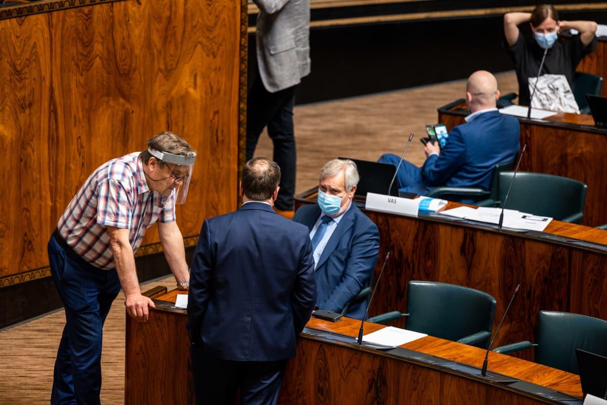 Kimmo Kiljunen, Ville Tavio ja Antti Rinne keskustelivat elpymispakettikeskustelun tauolla eduskunnassa 14.5.2021.