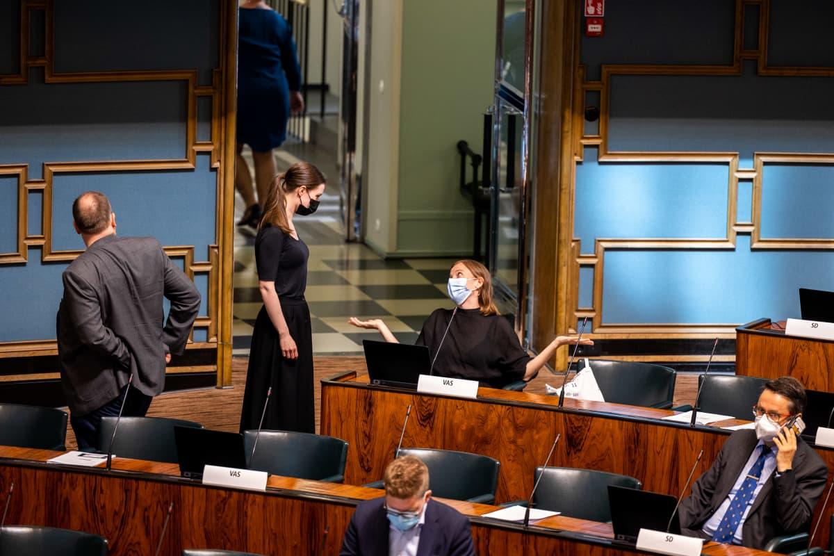 Sanna Marin ja Li Andersson keskustelemassa EU:n elpymispaketti -istunnon tauolla eduskunnassa.