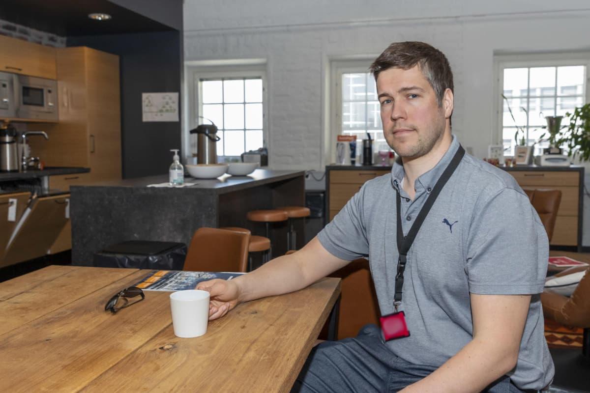 Jaakko Kaski pöydän ääressä kahvikuppi kädessä.