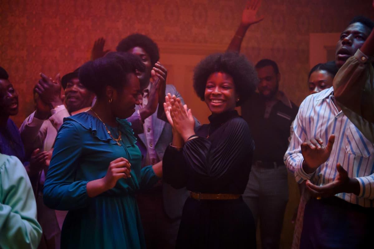 Ihmiset tanssivat punasävyisessä huoneessa.