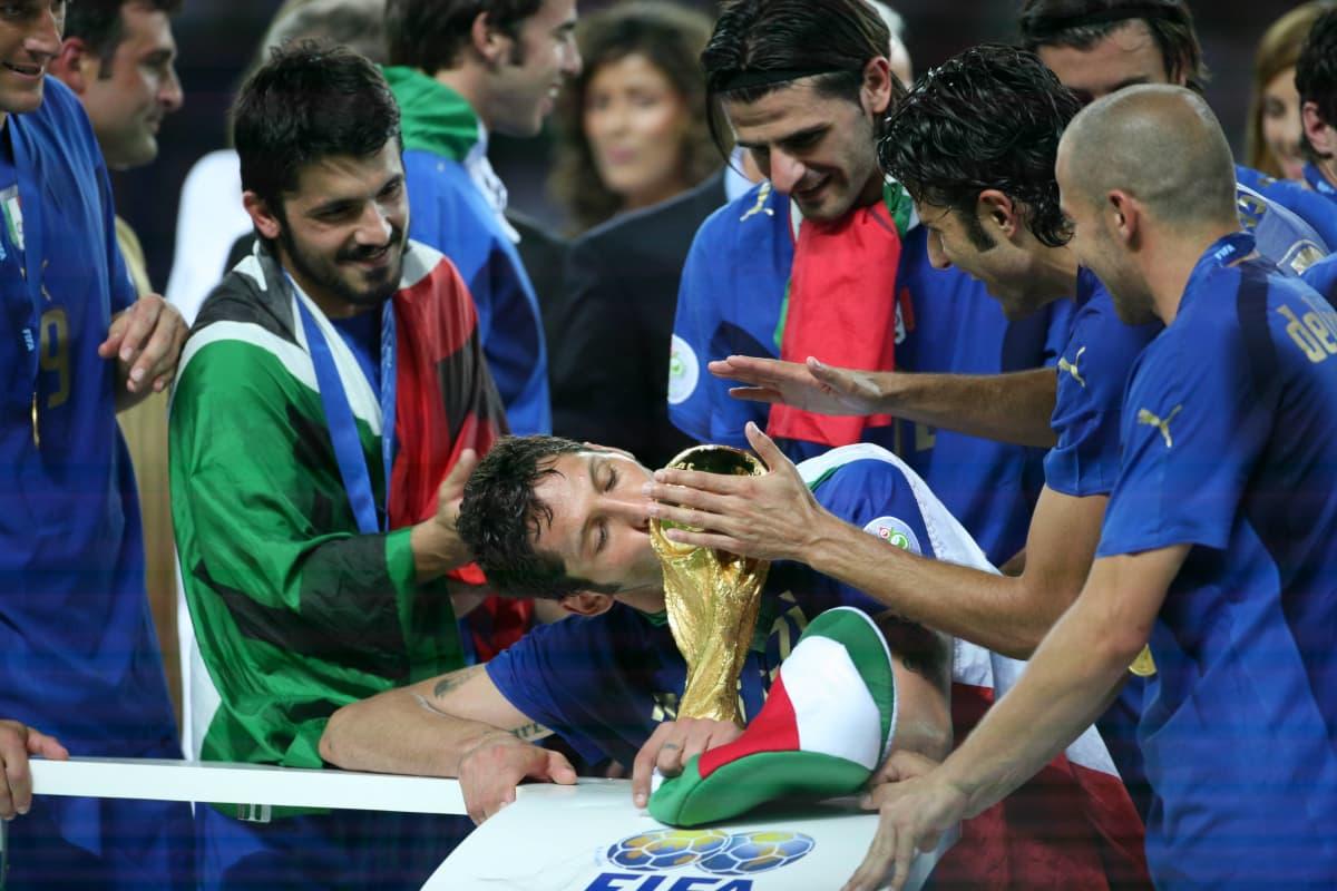 Italian pelaajia peliasuissaan palkintopokaalin ympärillä
