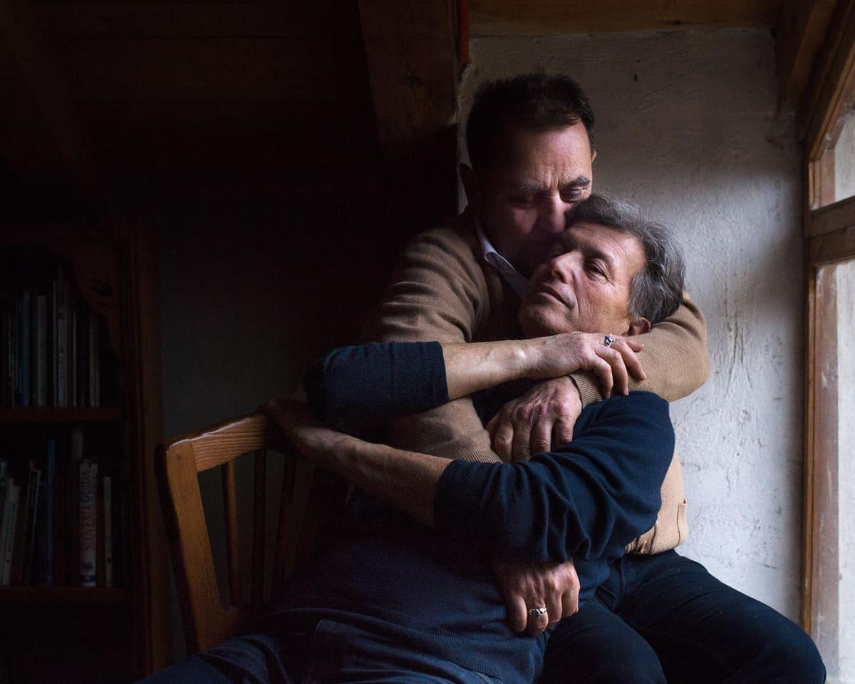 Valokuvateos, jossa kaksi miestä syleilevät toisiaan hämärässä huoneessa ikkunan valossa.
