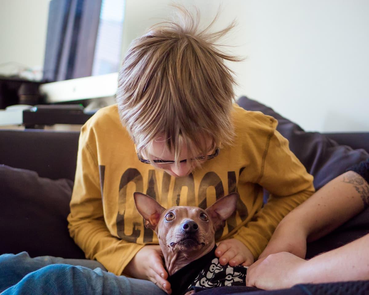 Tiitus Villman leikkii Ella koiran kanssa.