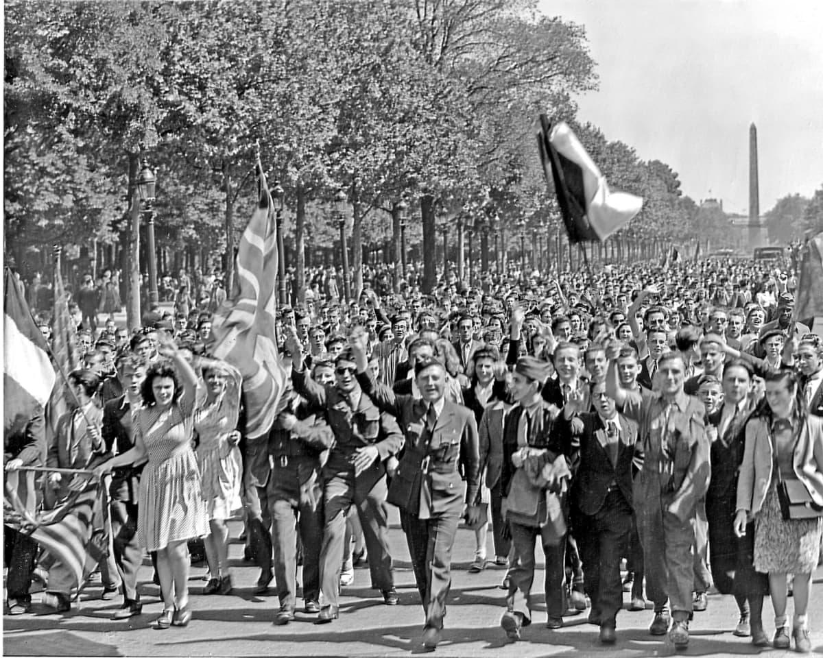 Ihmiset heiluttavat lippuja kadulla