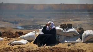 Palestiinalaisnainen suojaa hengitysteitään Israelin joukkojen kyynelkaasulta.