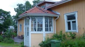 keltainen talo, etualalla lasikuisti