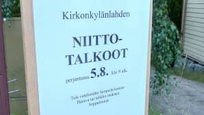 kyltissä teksti Kirkonkylänlahden niittotalkoot perjantaina 5.8. klo 9 alk.