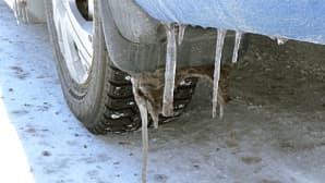 Kuvassa lähikuva auton talvirenkaasta, jonka takana roikkuu roiskeläpästä jääpuikkoja.