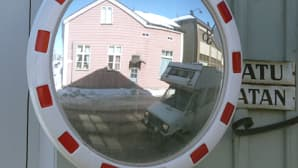 Kuvassa katupeili risteyksessä. peilistä näkyy ohiajava matkailuauto. Aurinko paistaa, maassa on lunta.