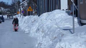 Kuvassa korkeita lumikinoksia kapealla puutalokaupungin kadulla. Iäkäs nainen potkukelkkailee kadulla.